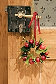 Wreath of holly leaves & ornamental apples on door handle