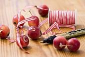 Zieräpfel mit kariertem Bändchen und goldfarbenem Stift
