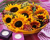 Sunflowers, guelder rose berries & grasses in yellow bowl