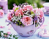 Small posy of pink roses and gypsophila in teapot