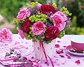 Arrangement of roses & lady's mantle on table laid in pink