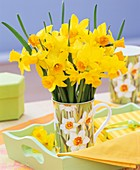 Bunch of narcissi in beaker on pale green tray