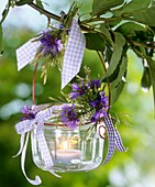 Windlight with cornflowers & white melilot on branch of cherry tree