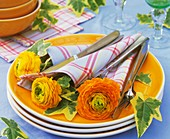 Yellow ranunculus in napkins with cutlery on pile of plates