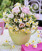 Arrangement of tulips, narcissi, wax flowers in pale green jug