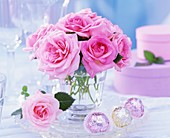 Pink roses in glass, chocolates and gift boxes beside it