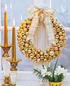 Fensterkranz aus goldfarbenen Weihnachtsbaumkugeln
