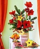 Arrangement of amaryllis, winterberries, fir branches in vase