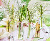 White and green asparagus in glass bottles on laid table