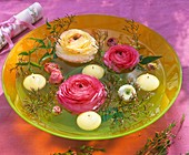 Ranunculus flowers, jasmine shoots & floating candles in bowl