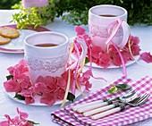 Wreath of pink hydrangeas around mugs of tea