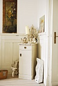 Silverware and candle on cabinet in corner of room with half-height wood panelling