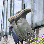 Rubber boots hanging on the wall of a greenhouse