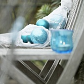 Christmas decorations in garden: baubles & candles in glasses on chair
