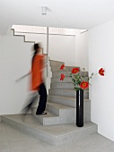 Woman walking up a modern, purist staircase and decorative poppies in black vase