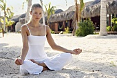 Woman in lotus position on sandy beach