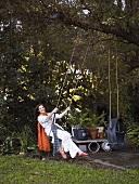 Woman sitting on swing in garden