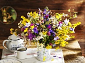 Vase of wild flowers on rustic wooden table