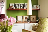 Modern cabinet with matching wooden shelf holding family photos against green-painted wall