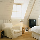 White armchairs next to dormer window in attic bedroom with white wood panelling