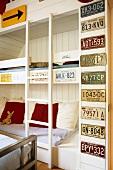 Schlafraum mit eingebautem Stockbett und aufgehängter Autokennzeichen-Sammlung