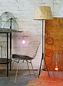Classic wire chair and 50s-style standard lamp surrounded by lampshade frames in artistic lighting workshop