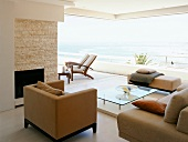 Modern sofa set in front of open glass wall with view of terrace and sea
