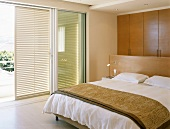 Double bed with partition headboard in modern bedroom with shutters on wide sliding windows
