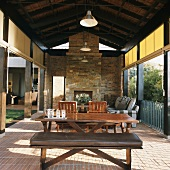 Outdoor living-dining room - terrace with rustic fireplace under exposed roof structure and roller sun screens on either side