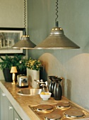 Kitchen counter with pendant lamps above hob and round sink in concrete worksurface