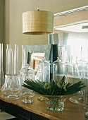 Various, empty glass vessels and arrangement of leaves in bowl next to mirrored top of dresser