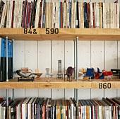 Ausschnitt eines selbstgebauten Bücherregals mit Modellen von klassischen Designer Sitzmöbeln