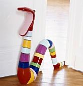 Gestreifte, bunte Schlangen-Skulptur mit offenem Maul auf dem Parkettboden im Türspalt