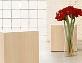 Ein Vase mit Amaryllis und Holzhocker