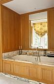 Eingebaute Badewanne mit Marmor-Einfassung und Holzvertäfelung mit integriertem Spiegel