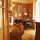 Blick in traditionellen Wohnraum auf eine Arbeitsecke mit Stilmöbeln und gestreifter Tapete mit Bildergalerie