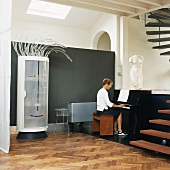 Whimsical cylindrical cupboard with stylised face and hair next to woman playing piano in loft apartment with open staircase