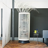 Round designer cupboard with stylised face in frosted glass door and punk hair in loft-style interior