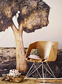 Fabric hats on wooden chair against photo wall mural of exotic tree