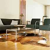 Wohnraum mit Designer Couchgarnitur und modernem Tisch auf Kuhfell