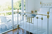 Metal bed frame with brass ornaments and view of white wicker chair through open terrace door