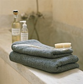 Towels, bath brush and bath essences on edge of bathtub