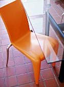 Orange plastic chair and modern glass table on terracotta tiles