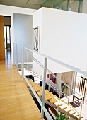 Gallery landing and head of open staircase leading down to living area in contemporary house