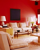 Dark blue painting above pale sofa set on bright red wall