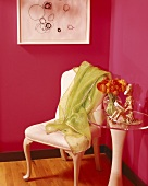 Corner of magenta room with lime green cloth on chair and side table with clear acrylic top