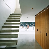 Minimalist staircase with cantilever concrete treads and photo projected onto hall wall