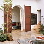 Gefliester Innenhof im orientalischen Stil mit Brunnenschale und Blick durch ein Holztor auf eine Sitzecke mit Beistelltischen
