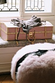 Lingerie on pink vintage suitcase and bundle of faux fur with black ribbon