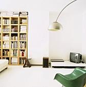 Medienecke auf niedrigem Tisch neben Bücherregal mit japanischem Hocker, 50er Jahre Designer-Sessel und Bogenlampe im Vordergrund